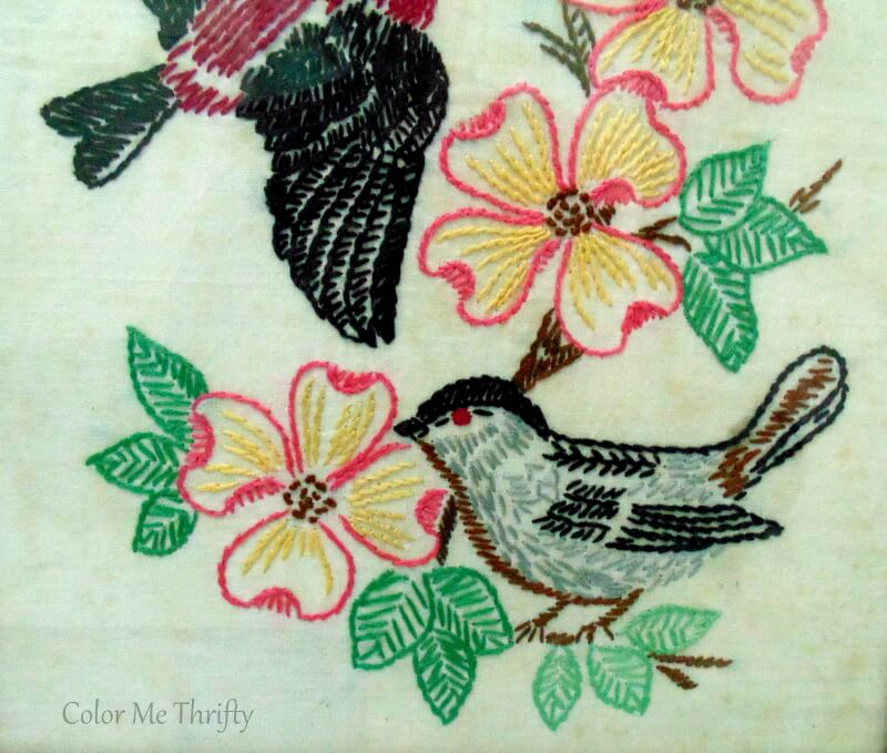 close up of light blue bird and pink flowers needlework