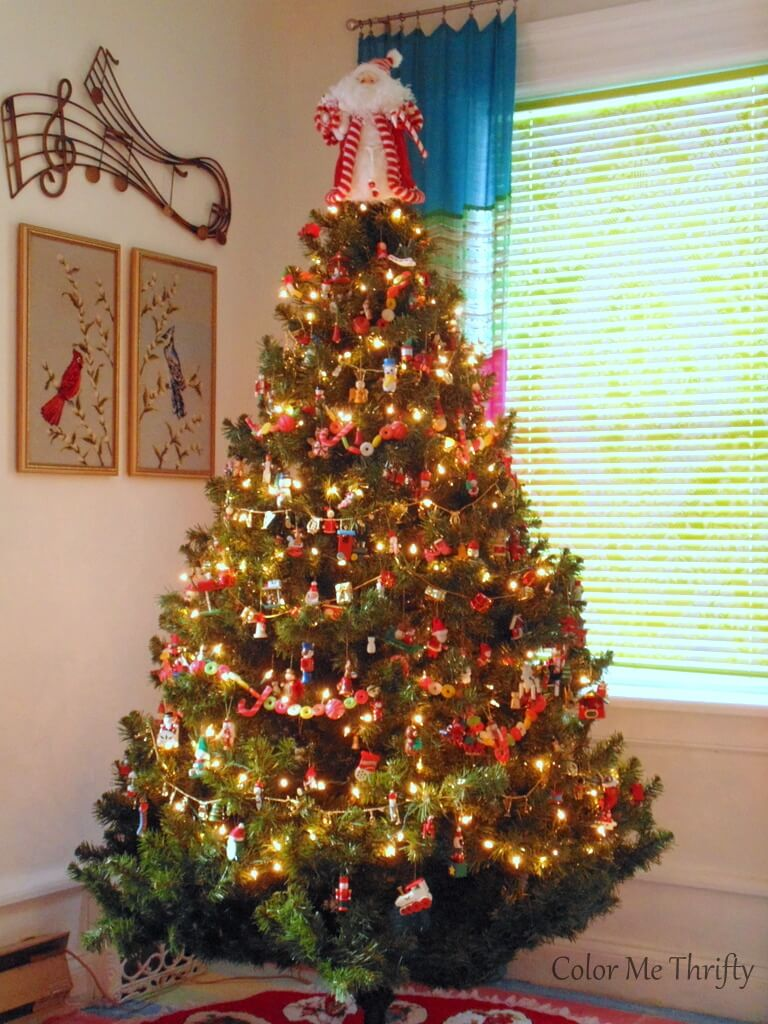 Christmas tree decorated with collection of vintage hand painted wooden ornaments