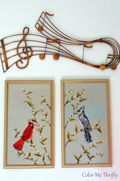 vintage bird needlepoint pictures and gold metal music scale wall decor vignette