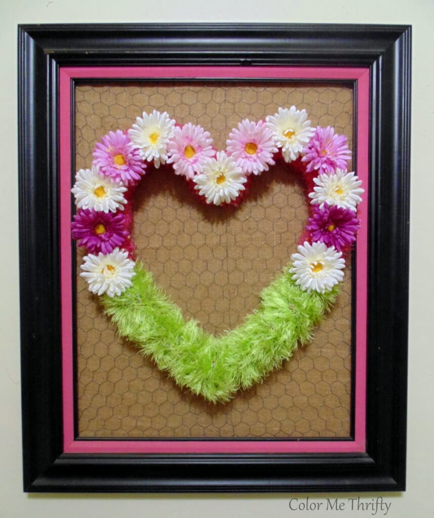 Floral heart wreath displayed on frame with chicken wire and burlap