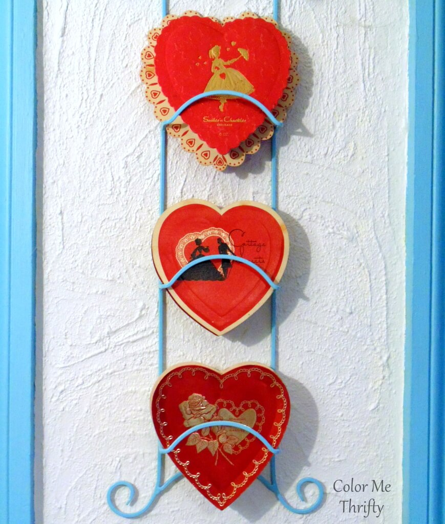 Vintage Valentine's Day chocolate boxes displayed in spray painted plate hanger