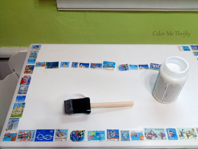 applying postage stamps to top of table with paper decoupage medium