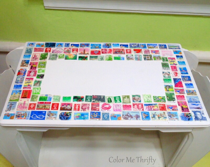 blue red and green stamp design on decoupaged table top