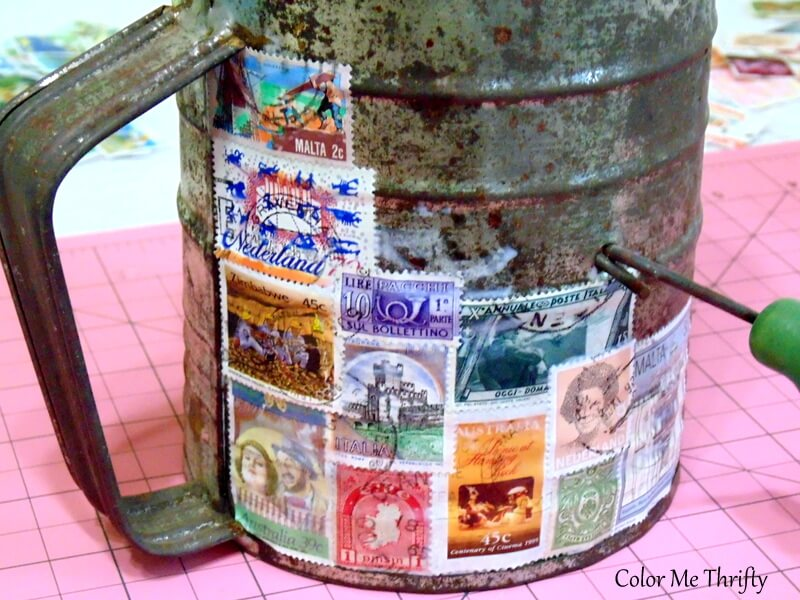 creating a mosaic of decoupaged postage stamps onto metal sigers