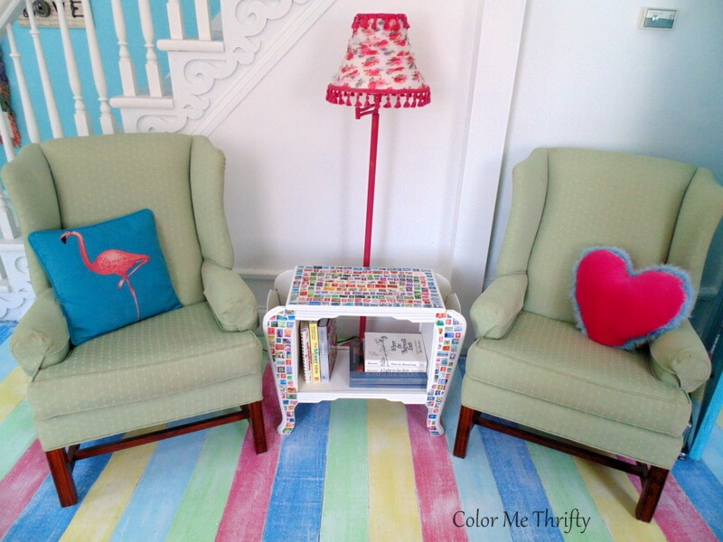 decoupaged postage stamp table between wing chairs in living room