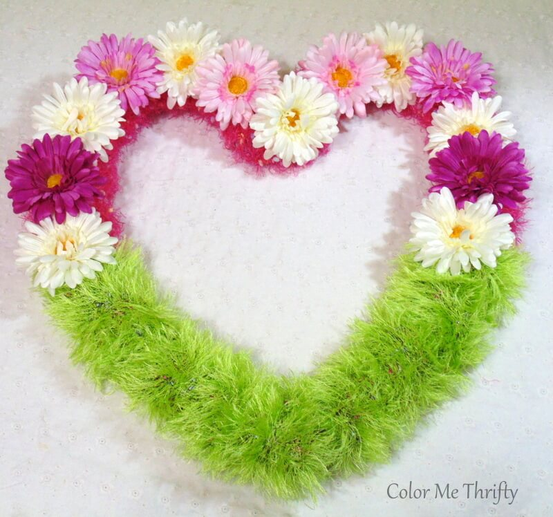 hot glued flowers onto pink scarf for floral heart wreath
