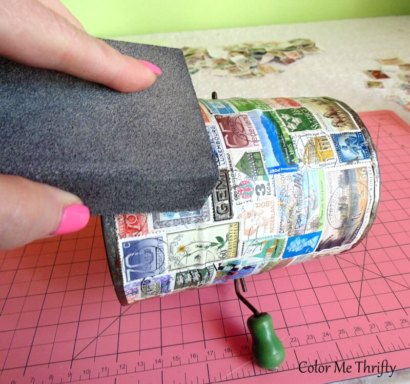sanding the decoupaged stamps on sifter with sanding block