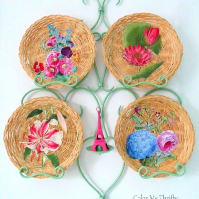 Repurposed wicker plates decoupaged with floral graphics and displayed in plate rack with Eiffel Tower
