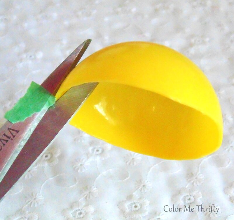 cutting slits into plastic balls halves with scissors