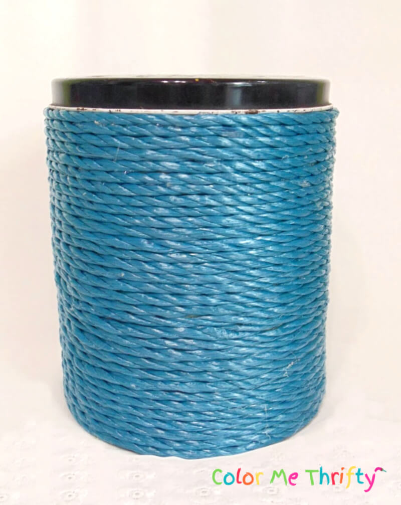 metal canister covered with plastic blue woven rope