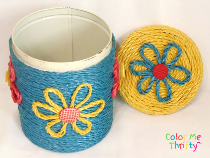 metal canister makeover with lid off showing rope flowers on lid and front