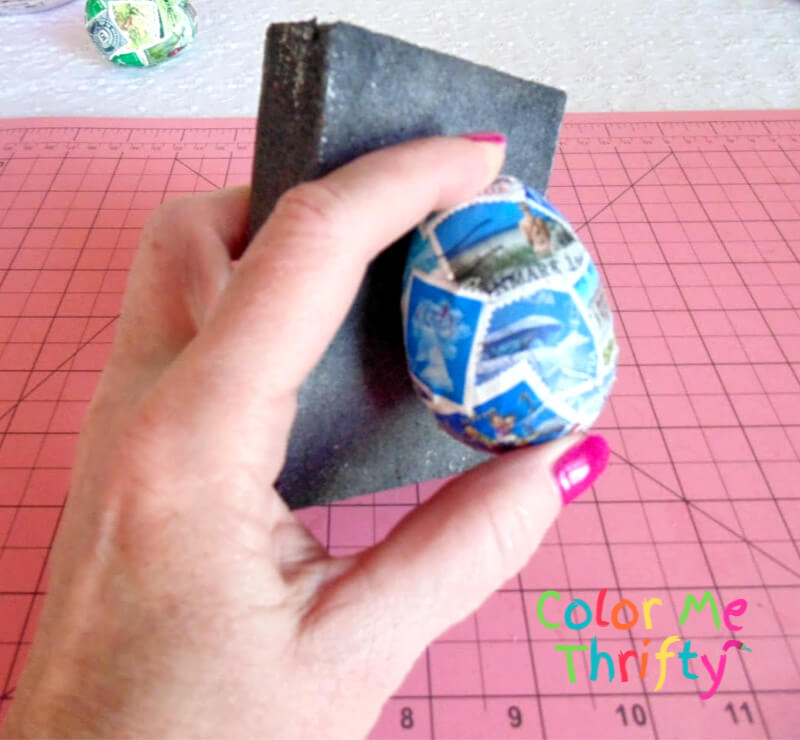 sanding Easter eggs decoupaged with postage stamps