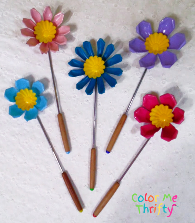 spray painted repurposed jello mold flowers with yellow ceners and fondue fork stems