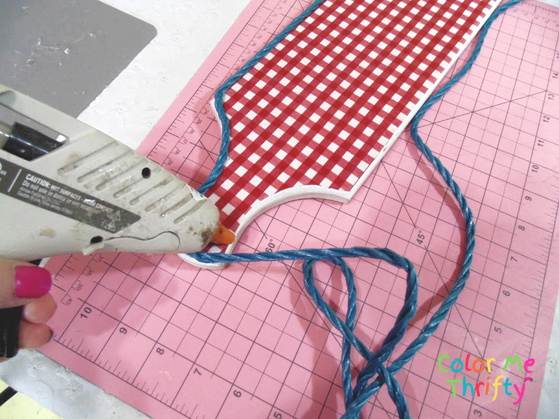 applying blue rope onto edges of decoupaged fabric cutting board sign