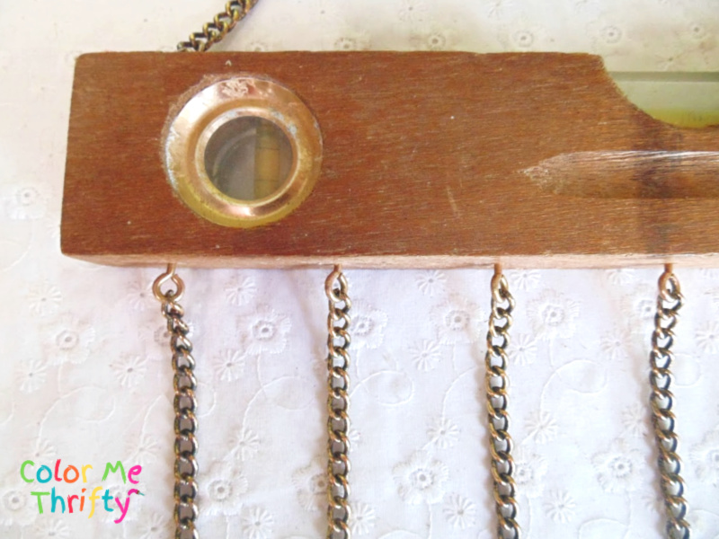 close up of necklace pieces attached to wooden level using eye hooks