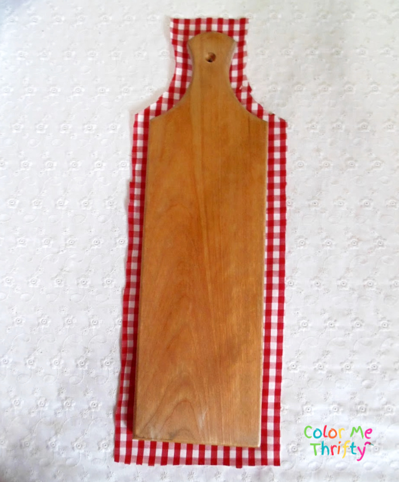 cutting red and white gingham fabric around cutting board