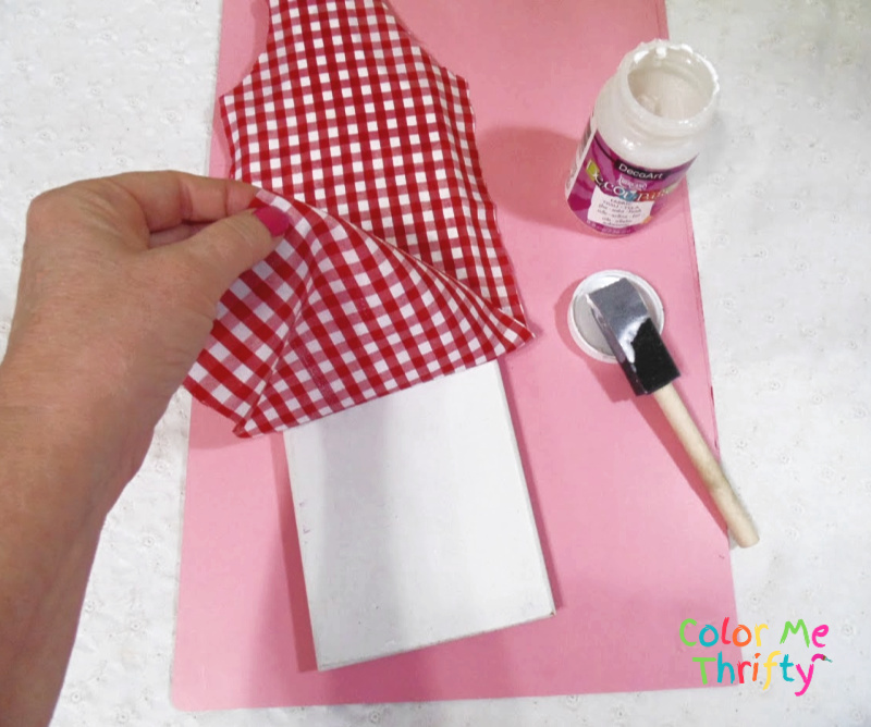 decoupaging red and white gingham fabric onto cutting board after it was spray painted white