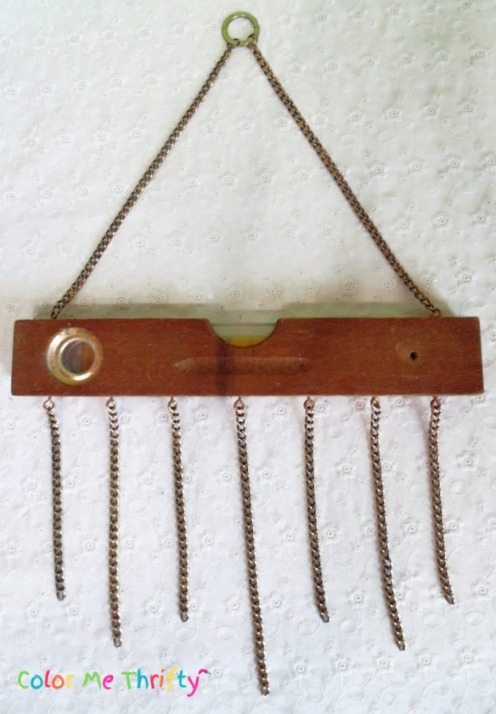 necklace pieces attached to wooden level using eye hooks