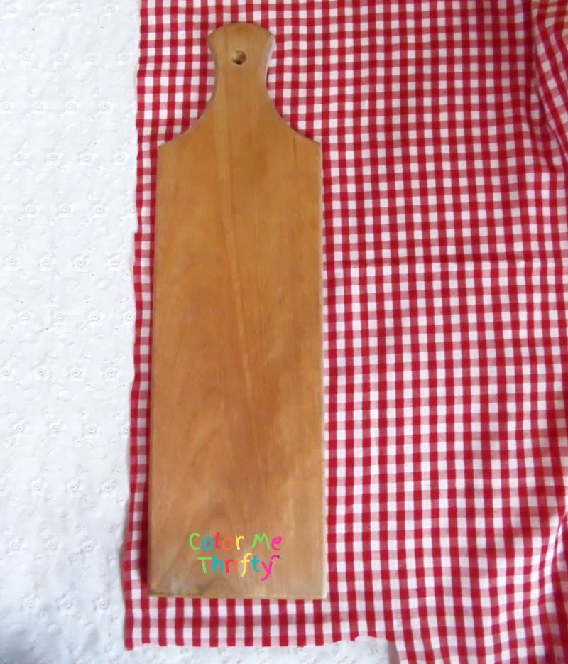 placing wooden cutting board on red and white gingham fabric