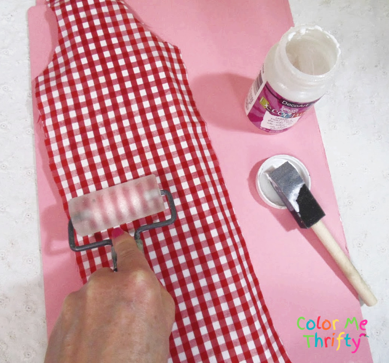 uisng breyer to smooth the decoupaged fabric onto wooden cutting board