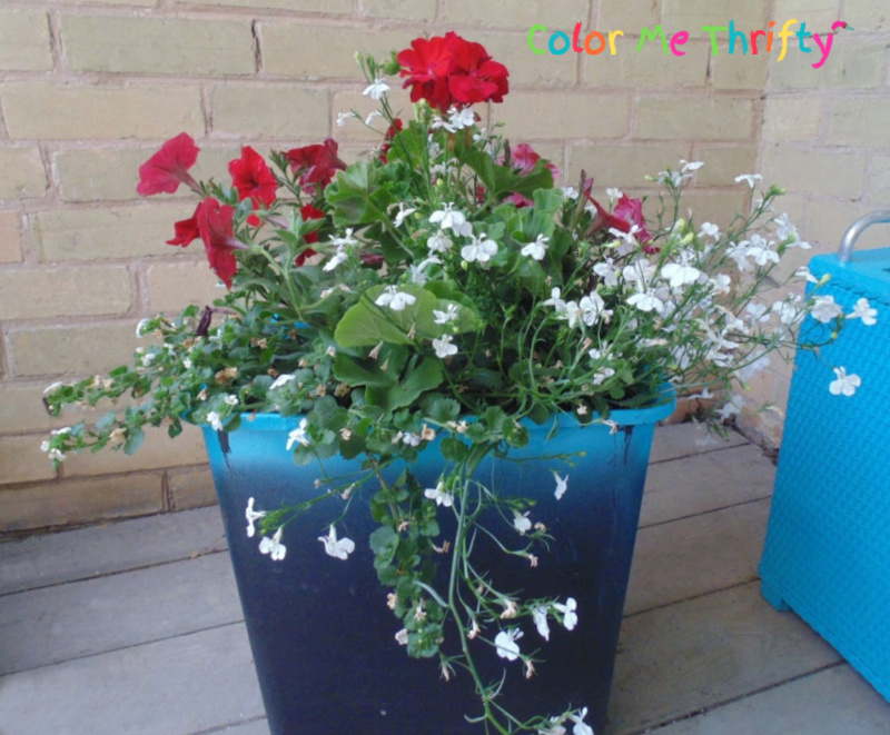 planting flowers in spray painted garbage can before putting into laundry hamper planter