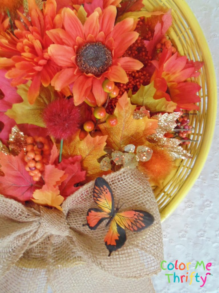 adding faux butterfly onto burlap ribbon bow on fall wreath
