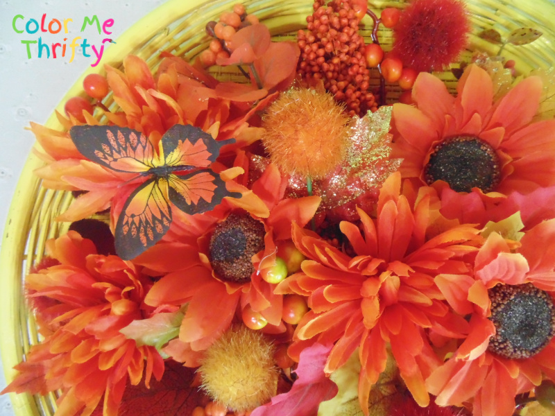 filling in colorful fall wreath with florals and leaves