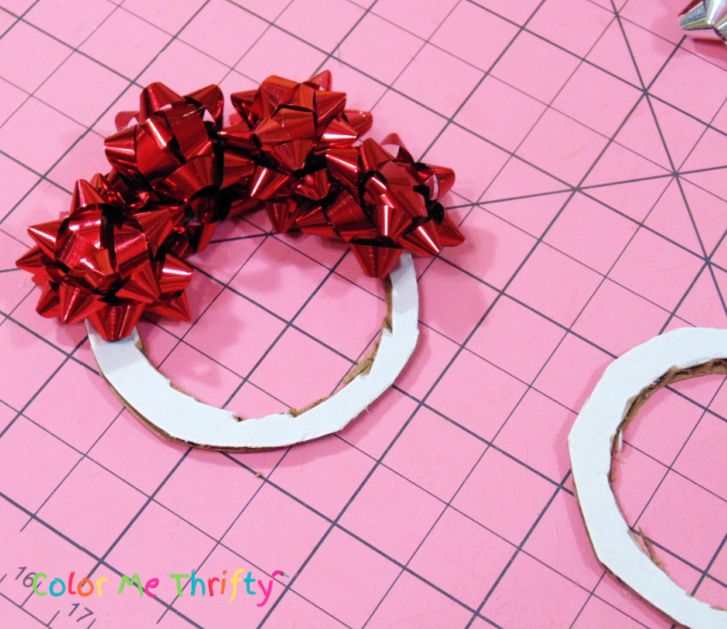 gluing miniature gift bows onto cardboard circles for diy tree ornaments