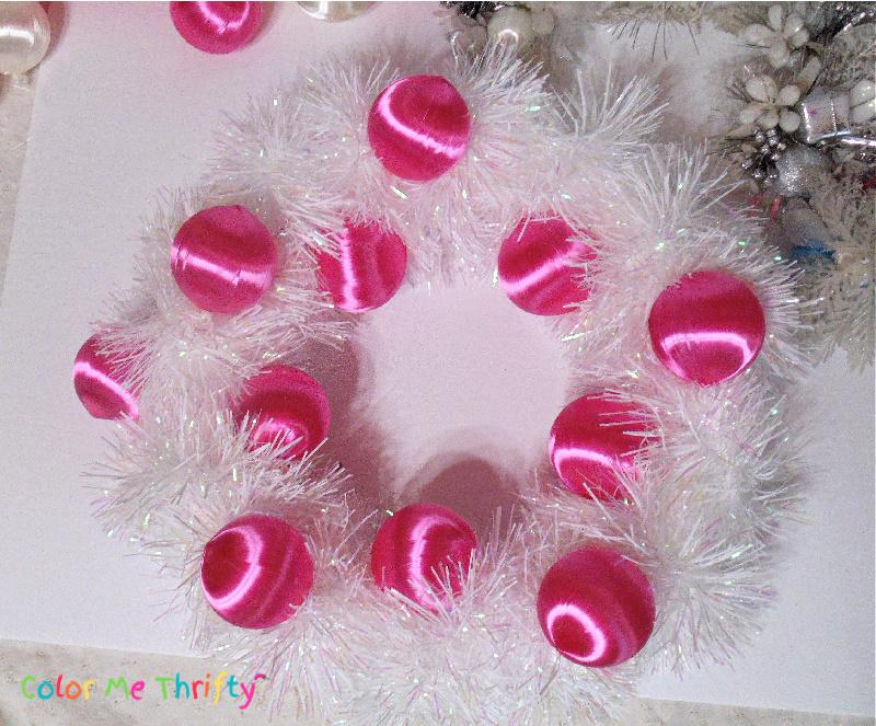 pink satin ball ornaments glued onto wreath form around white garland