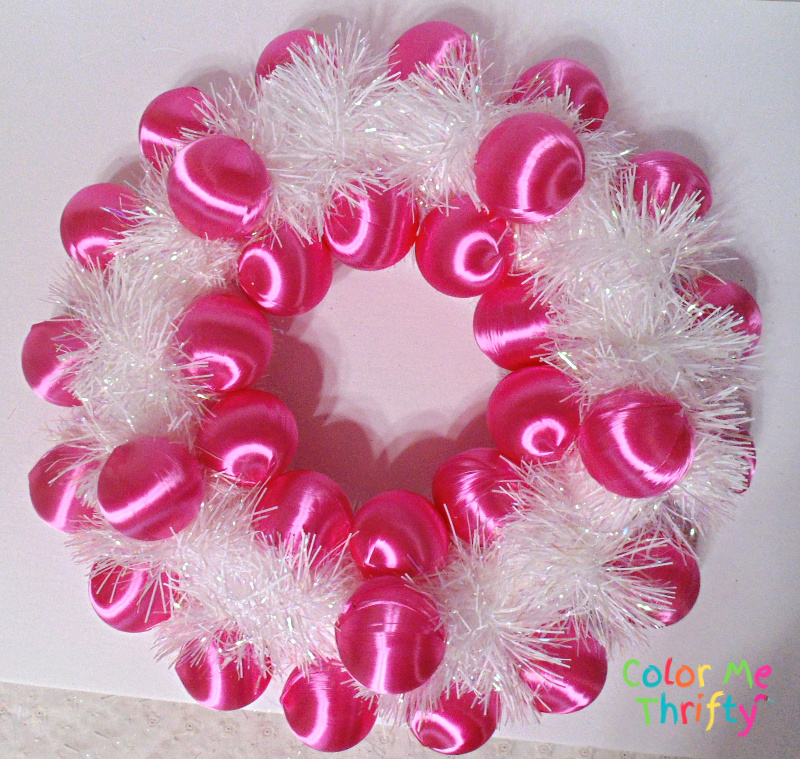 pink winter wreath starts to take shape with satin ornaments glued onto wreath form around white garland