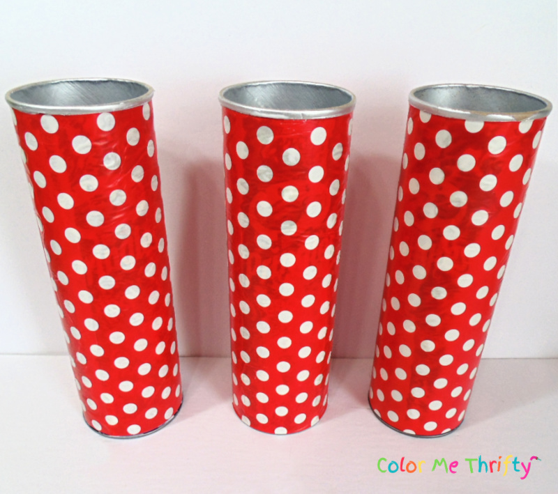 3 decoupaged pringles cans with red and white polka dot wrapping paper