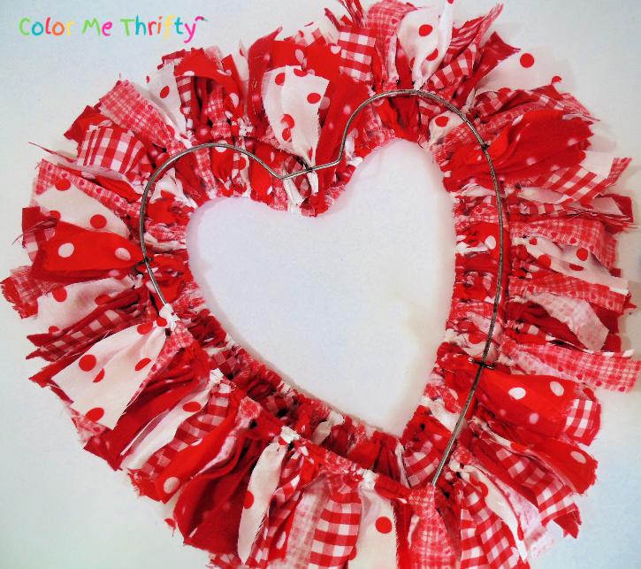 applying fabric strips onto bottom metal rim of heart wreath frame