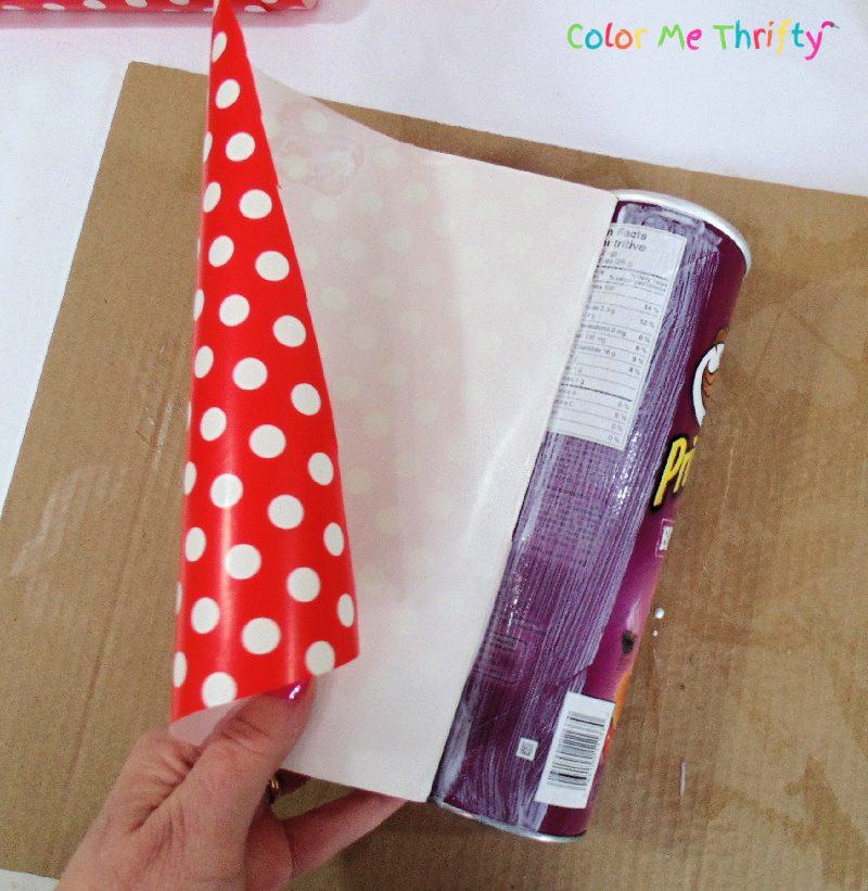 continuing to cover pringles can with decoupage medium and wrapping paper