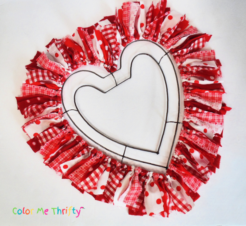 random pieces of fabric strips looped onto outside rim of heart wreath form