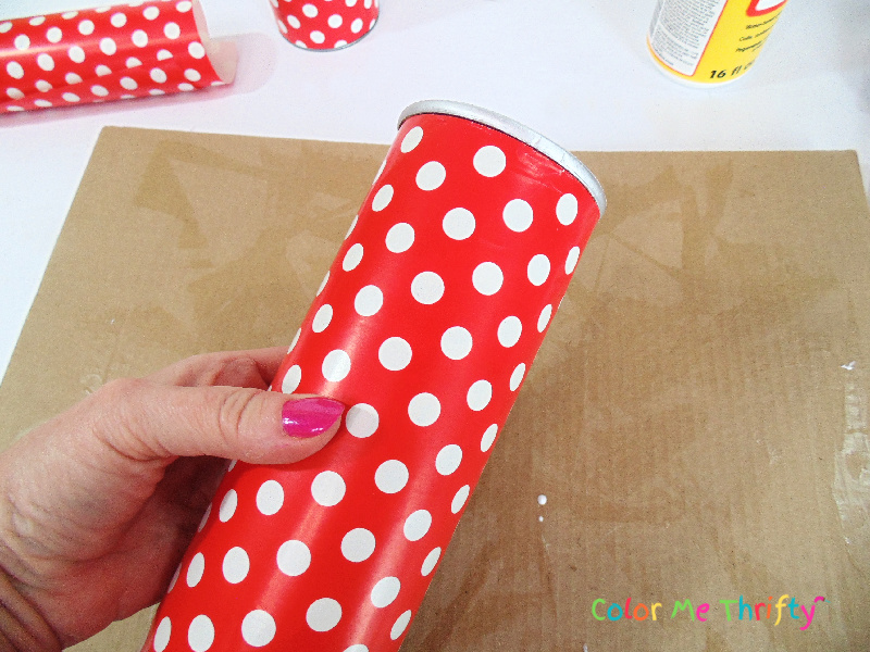 smoothing wrapping paper onto pringles can