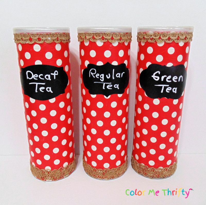 trio of Pringles cans decoupaged with wrapping paper with jute ribbon trim and chalkboard labels