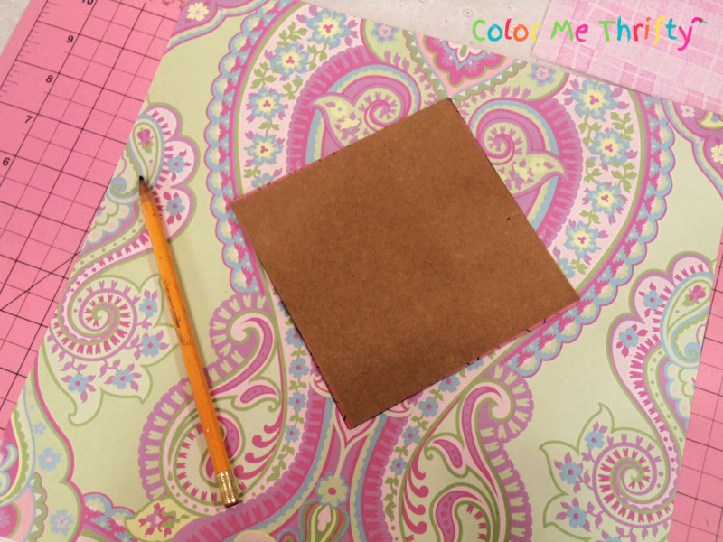 using cardboard template on an angle to cut scrapbook paper into pieces to create colorful patters