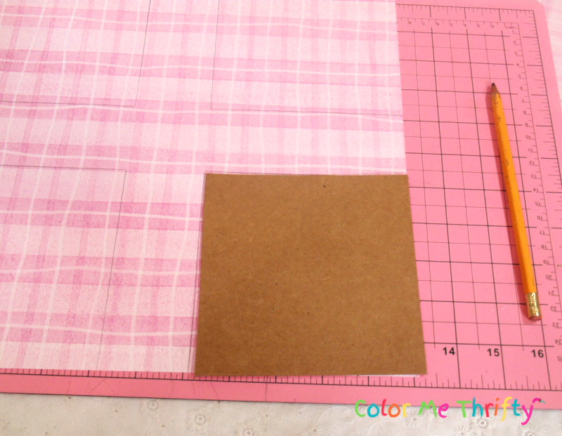 using cardboard template to cut scrapbook paper into pieces to create colorful patters