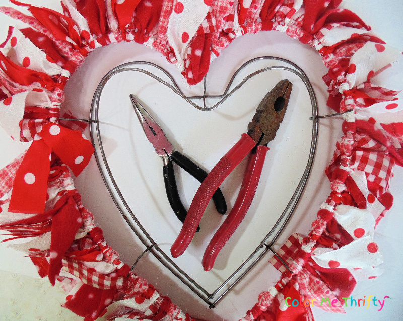 using pliers to bend the middle wire section of heart wreath frame into a better heart shape