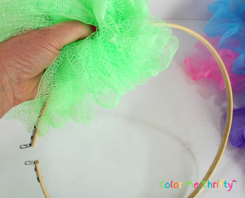 pushing the embroidery hoop through the shower pouf
