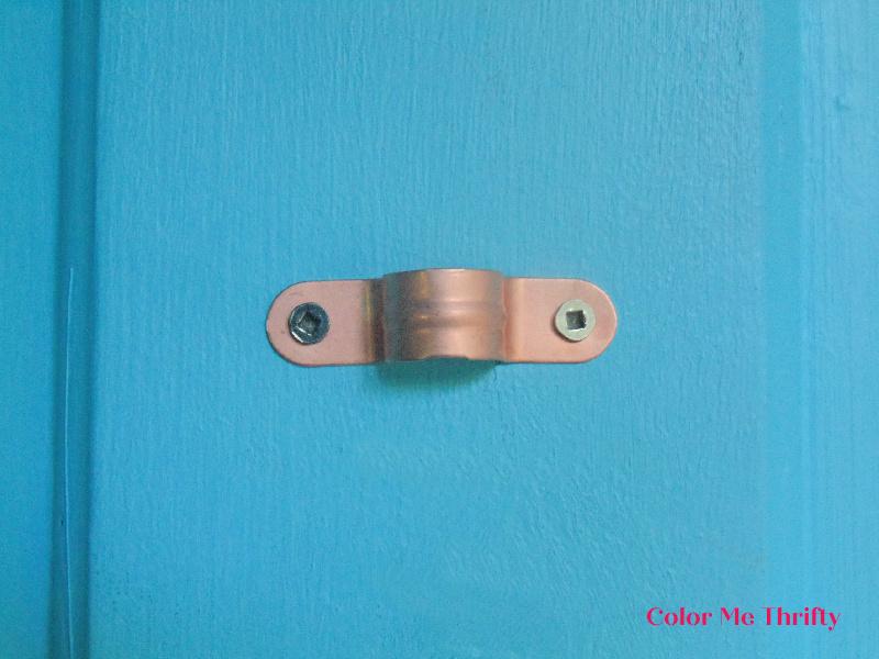 copper fitting used to hang junk flower door decor on door