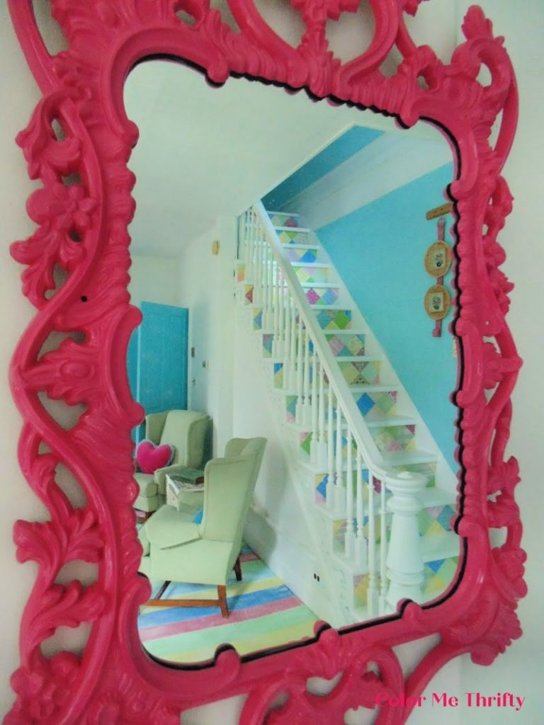 view of decoupaged stairs through vintage gold mirror after spray painted gold mirror makeover
