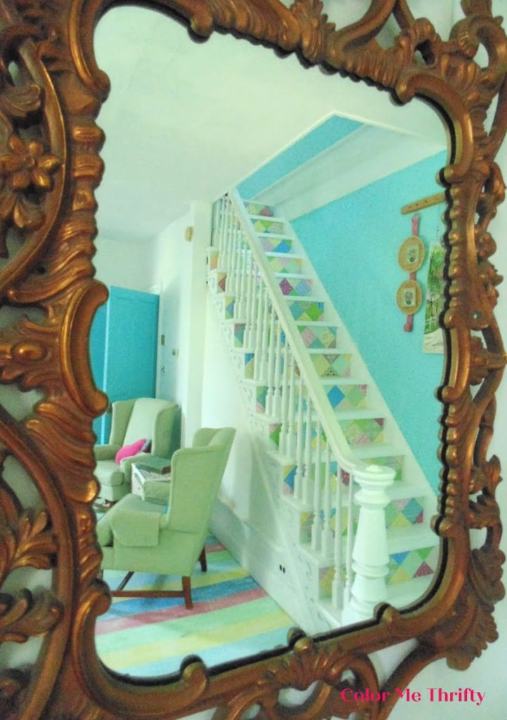 view of decoupaged stairs through vintage gold mirror before mirror makeover
