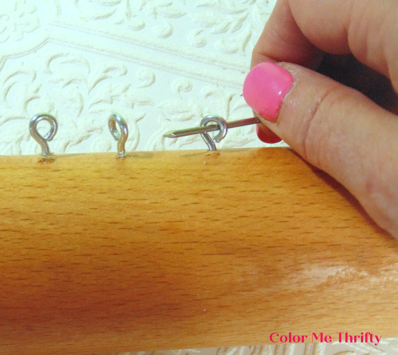 using a nail to twist metal screw eyes into wooden rolling pin for wooden spoon wind chimes