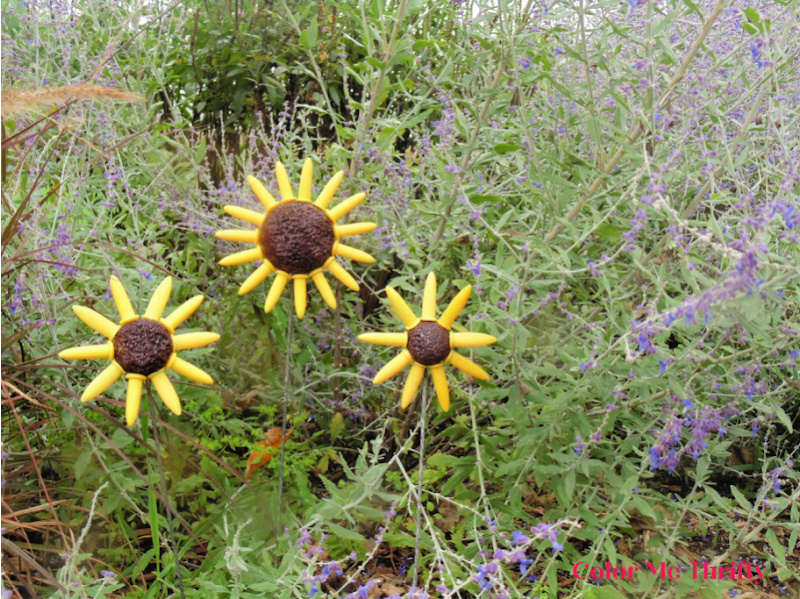DIY fall flowers from repurposed corn holders displayed in the garden with Russian Sage
