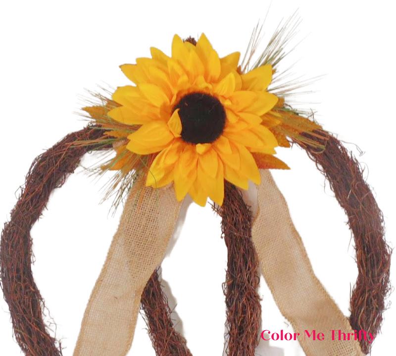 adding center sunflower bow to top of grapevine wreath below the pumpkin stem