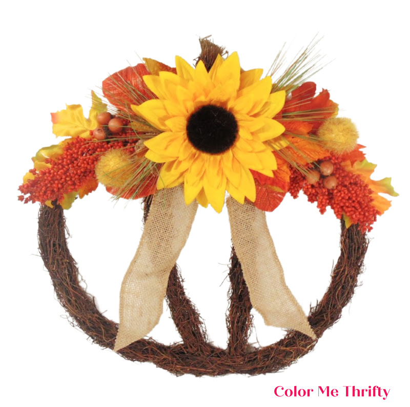 adding fall leaves and acorns to grapevine pumpkin wreath