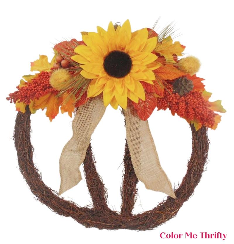 adding finishing touches to fall pumpkin wreath