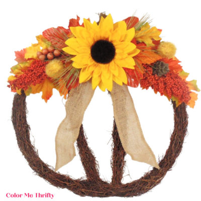 filling in fall pumpkin wreath with fall leaves and decorative berries