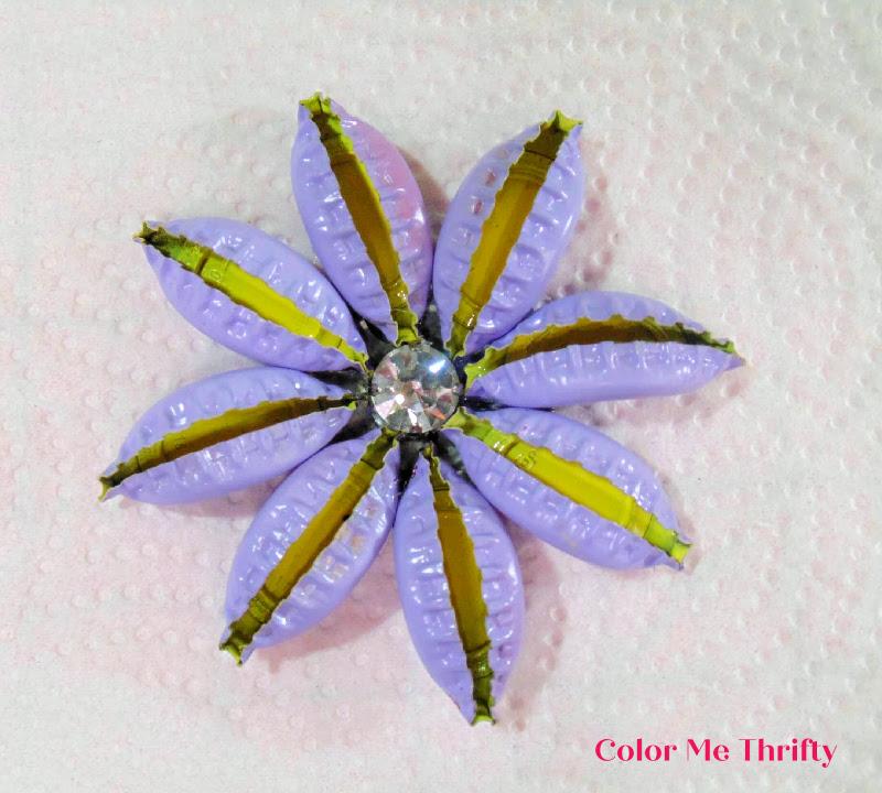 purple spray painted repurposed beer caps flower